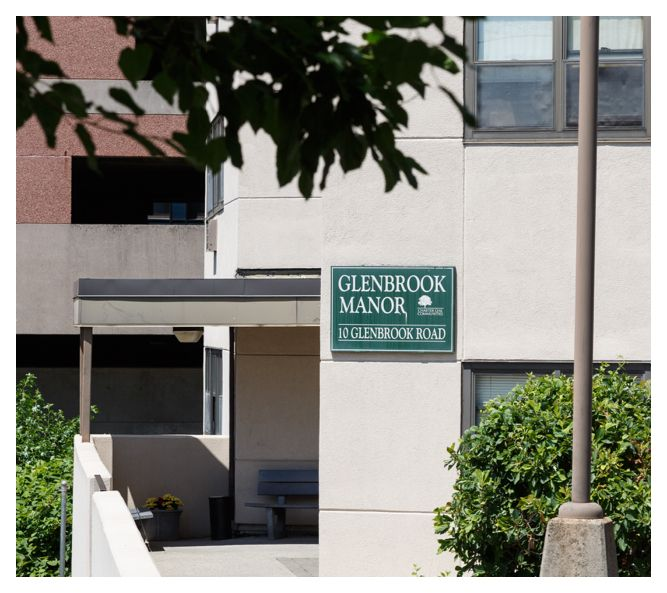 The Glenbrook Manor sign sits on the side of the concrete building next to the wheelchair-accessible, covered entrance.