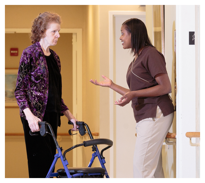A friendly registered nurse chats to a senior resident using a rollator.