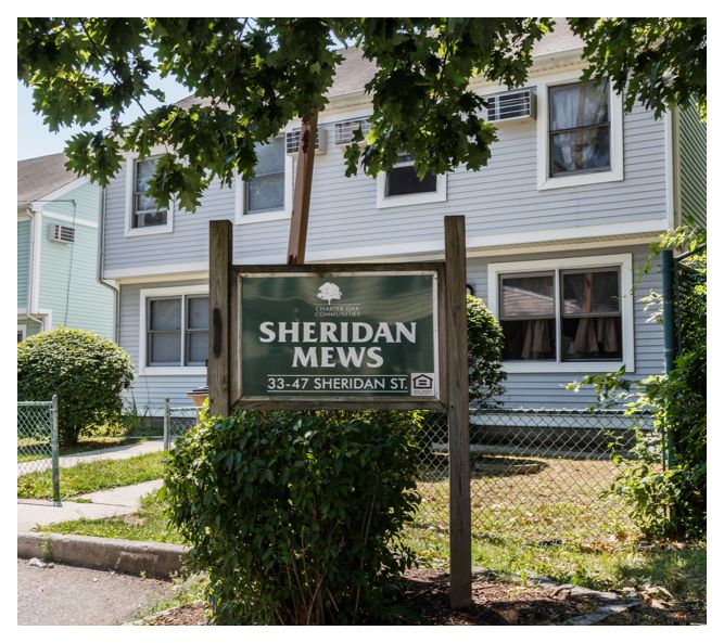 The Sheridan Mews sign sits near a shrub and in front of the first building. The building's windows are open, letting in fresh air.