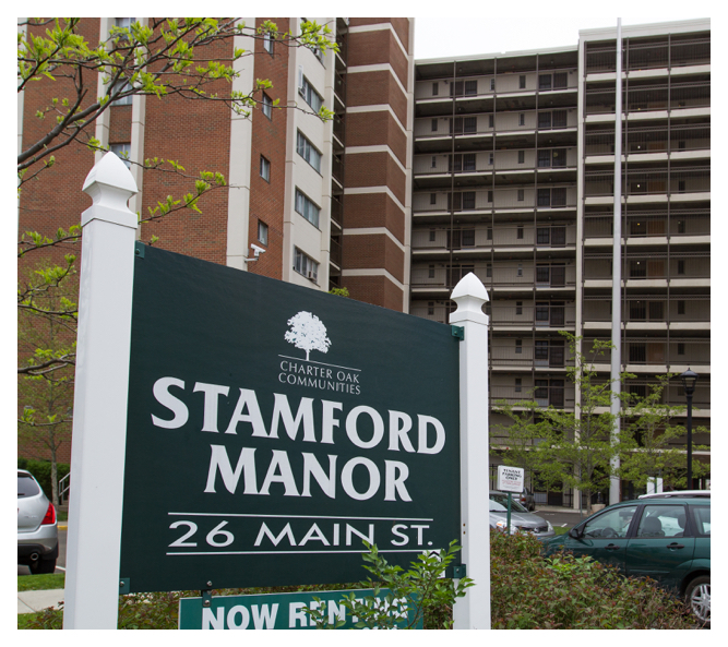 The large Stamford Manor sign sits in the parking lot with the impressive, eleven-story building towering behind it.