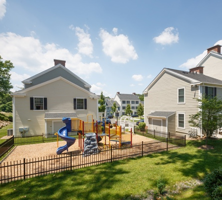 A sunny, outdoor communal area features a colorful playscape suitable for children near well-kept apartment buildings.