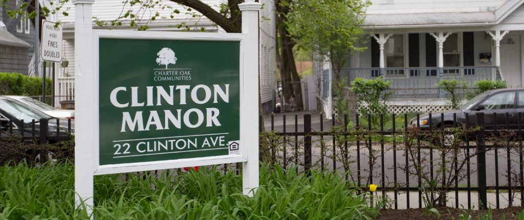 The quaint sign for Clinton Manor sits among plants and flowers and reads Clinton Manor, 22 Clinton Avenue.