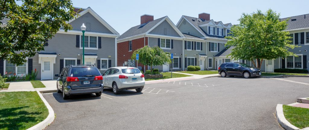 A dedicated parking area features standard and handicap parking spaces. Wheelchair accessible sidewalks line the area.