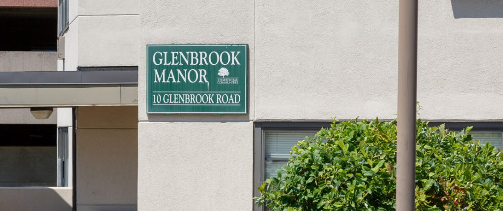 The square sign for Glenbrook Manor sits on the side of the concrete building and reads Glenbrook Manor, 10 Glenbrook Road.