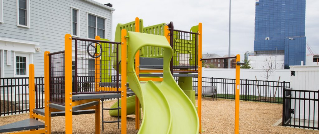 The brightly colored playscape has slides, ladders, stairs and more for children to play on, and a park bench for parents.