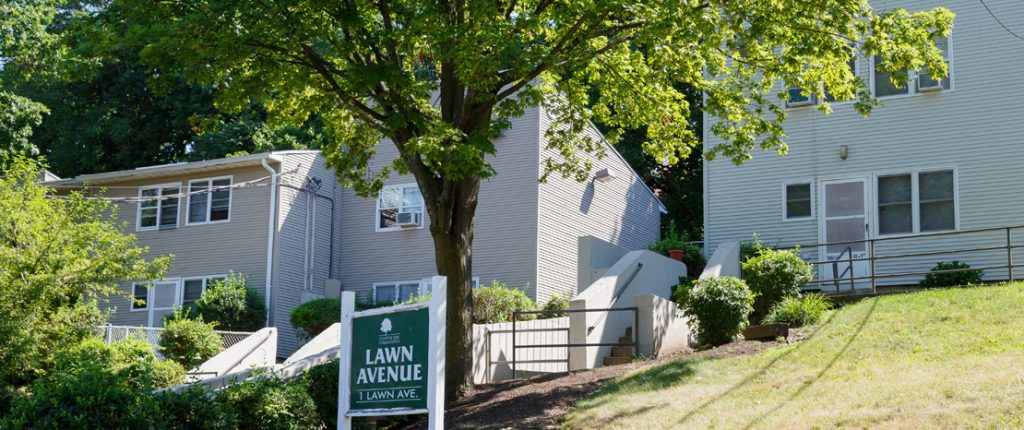The Lawn Avenue sign sits under a large tree behind the well-maintained townhouses.