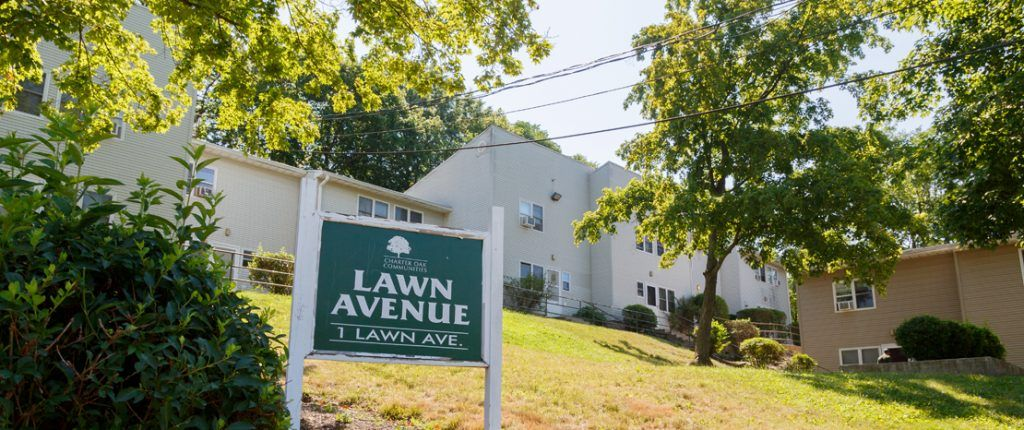 The Lawn Avenue sign sits in a large grassy area surrounded by the buildings; it reads Lawn Avenue, 1 Lawn Ave.