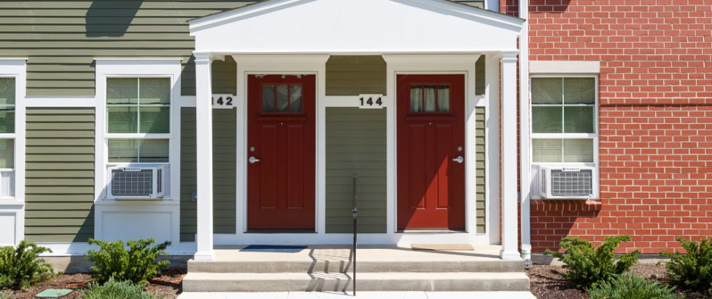 A landscaped covered entrance features Colonial elements and red doors. Window AC units are visible.