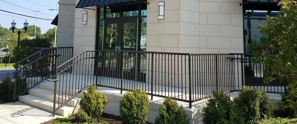 The contemporary entrance to Park 215 features stairs as well as a wheelchair accessible ramp punctuated by shrubbery.