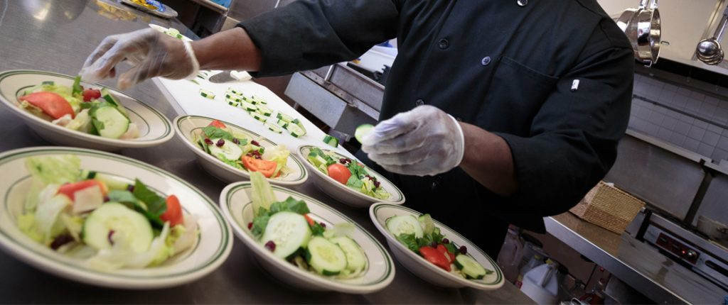 The on-site chef prepares six garden salads filled with fresh lettuce, wedge tomatoes, cucumbers, and more.