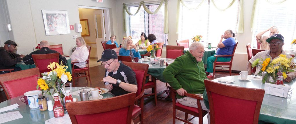 The light-filled dining area is full of residents enjoying their meals and each other's company.