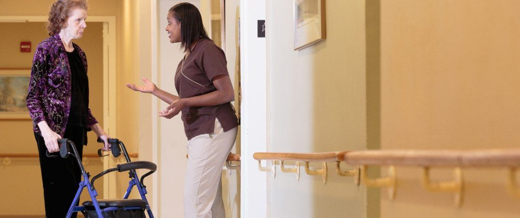 An on-site registered nurse engages a resident using a rollator in conversation. Support railings line the walls.