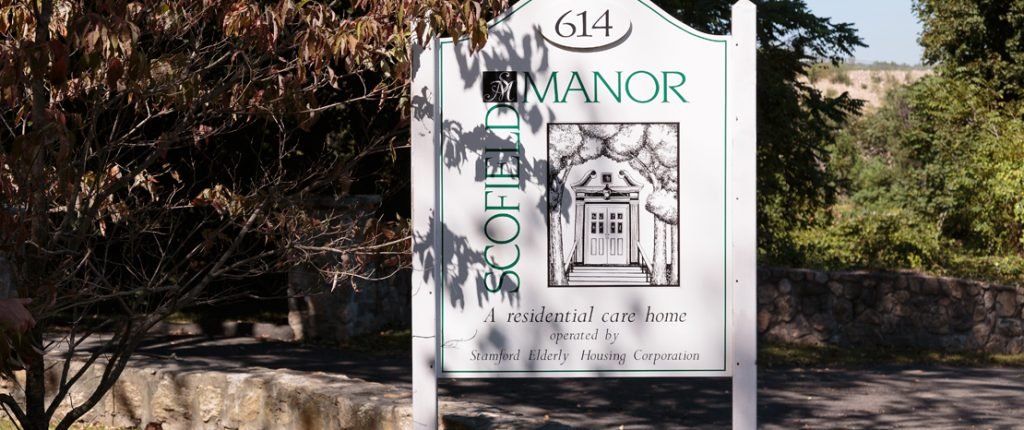 The Scofield Manor sign reads 614 Scofield Manor, a residential care home operated by Stamford Elderly Housing Corporation.