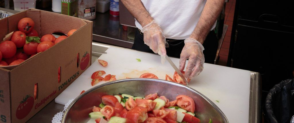 A chef cuts a tomato into wedges to add to a large bowl of cucumbers and tomatoes. A large box full of tomatoes sits nearby.