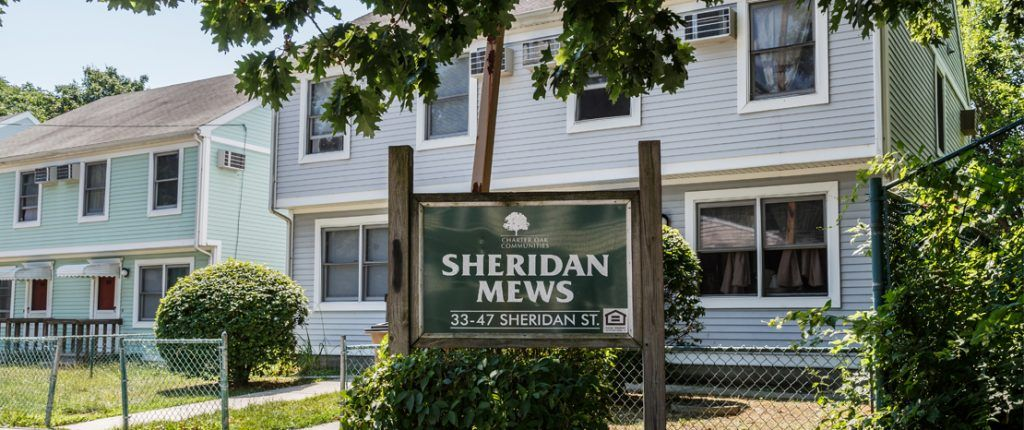 The wooden sign for Sheridan Mews features the Equal Housing Opportunity logo and reads Sheridan Mews, 33–47 Sheridan St.