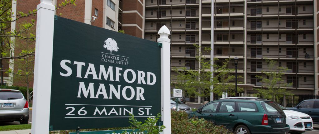 The sign for Stamford Manor sits amongst shrubbery and reads Stamford Manor, 26 Main St.