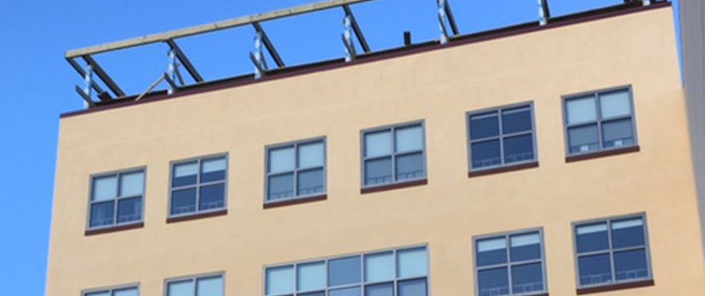 Looking up to the top of the building shows the many windows and a glimpse of the rooftop patio framework.