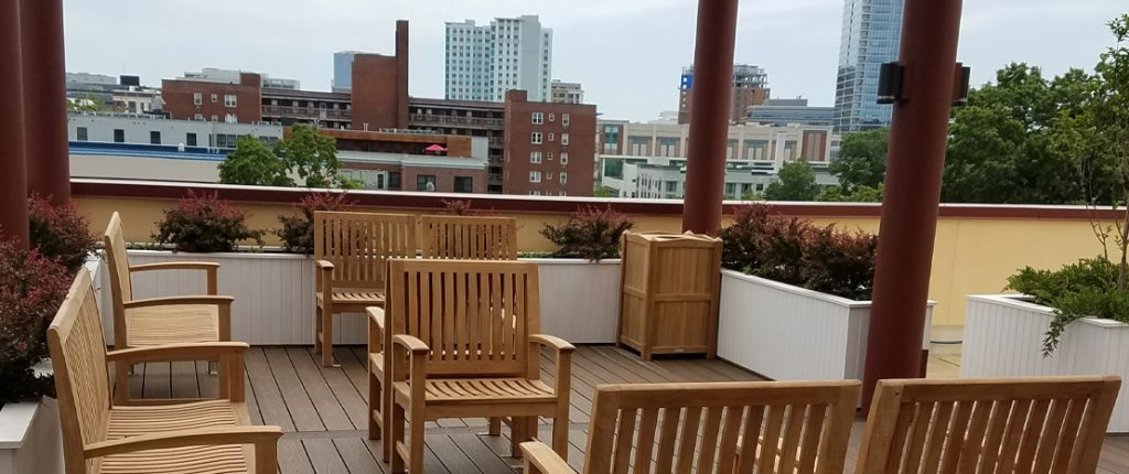 Summer Place's inviting rooftop patio features seating arranged to spark conversation, surrounded by boxed gardens.