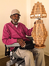 Clinton Manor resident Johnny Taylor sits in his motorized wheelchair, smiling while showing a unique, wooden lamp.